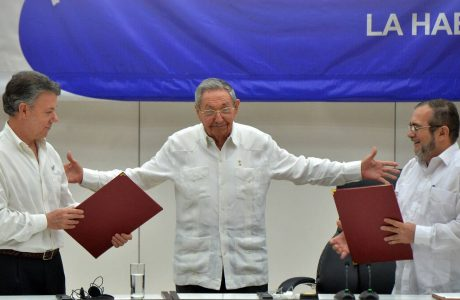 "Colombia's President Juan Manuel Santos (L) and Timoleon Jimenez, aka ""Timochenko"" (R), head of the FARC leftist guerrilla, hold folders with documents as Cuban President Raul Castro (C) gestures during the signing of the ceasefire in Havana on June 23, 2016. Colombia's government and the FARC guerrilla force signed a definitive ceasefire Thursday, taking one of the last crucial steps toward ending Latin America's longest civil war. / AFP PHOTO / ADALBERTO ROQUE"